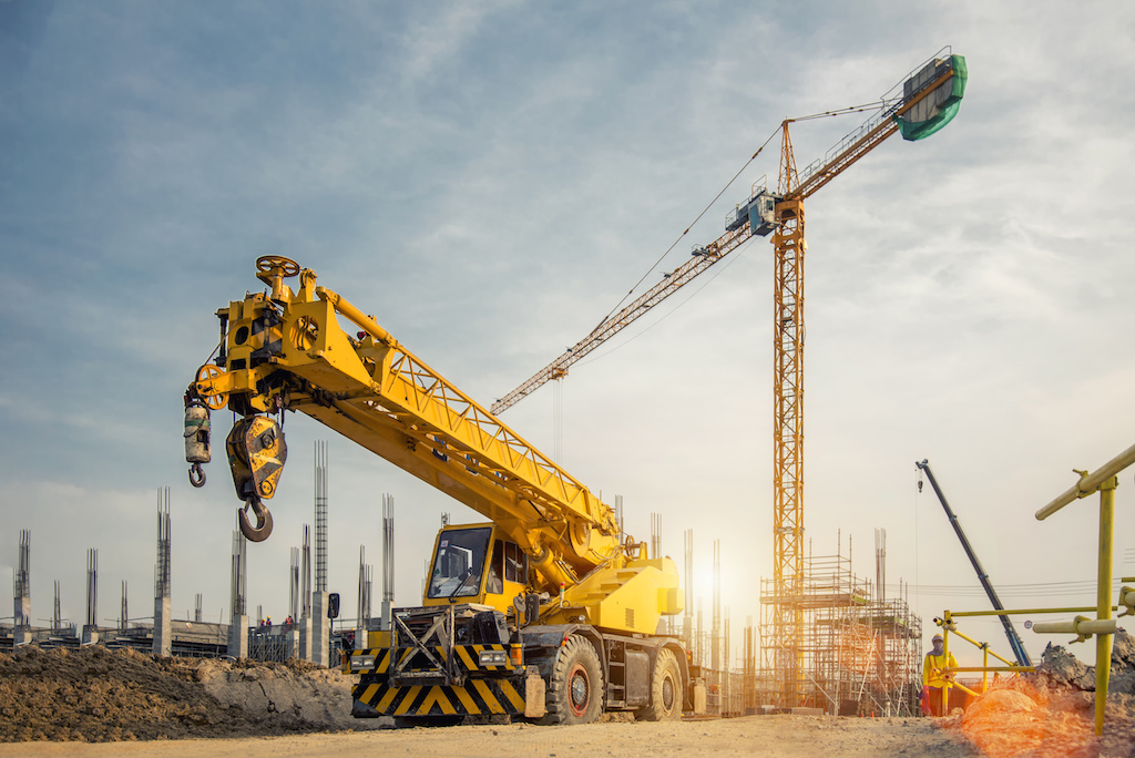 Mobile Crane on a road and tower crane in construction site - Construction  Plant News